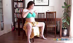 Eine reife Britin spielt mit ihren Titten